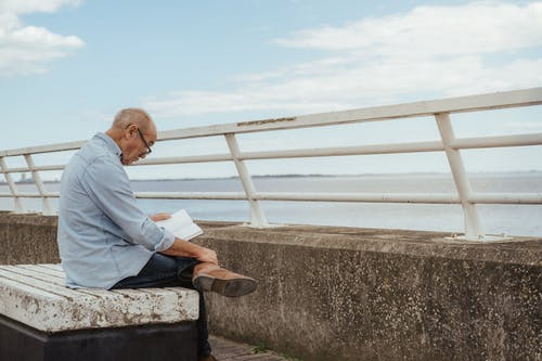 Side view of serious aged male wearing casual clothes and eyeglasses engaged in hobby reading book on embankment