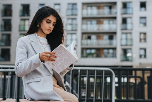 Low angle of serious ethnic female with makeup reading book while sitting on bench in park
