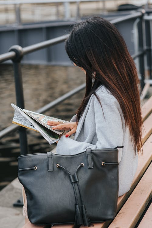 Woman reading magazine on bench at city waterfront
