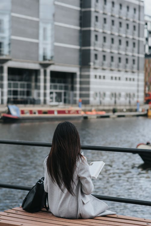 Back view of unrecognizable female in warm outwear sitting on bench on waterfront and reading book