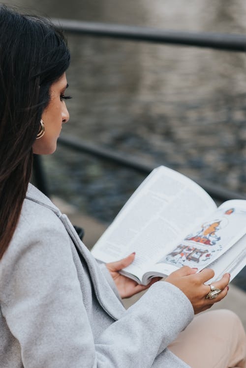 High angle side view of focused female reading literature while resting on city embankment