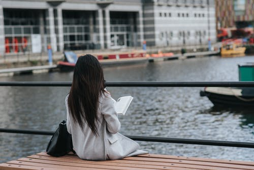 Back view of unrecognizable female in warm clothes reading book at spare time on waterfront