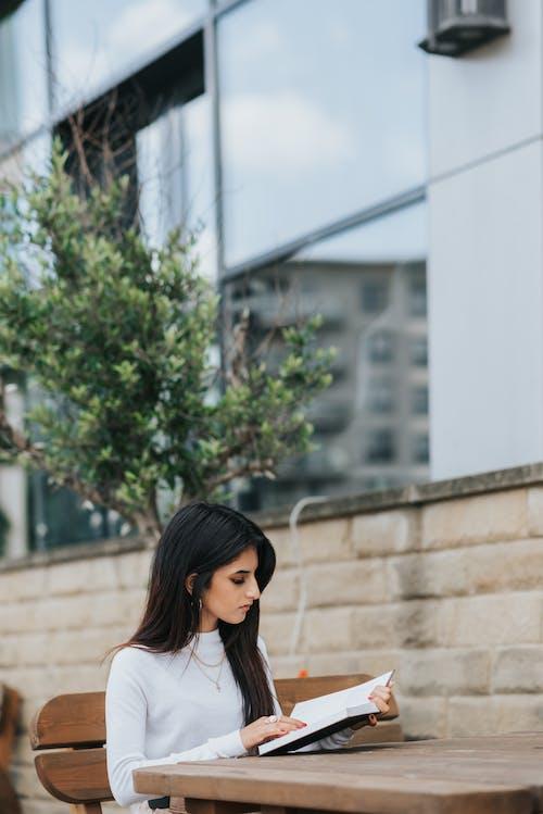 Pensive ethnic woman reading book on street