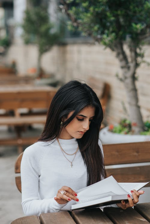 High angle of focused ethnic woman flipping pages of book while sitting at table in street cafe