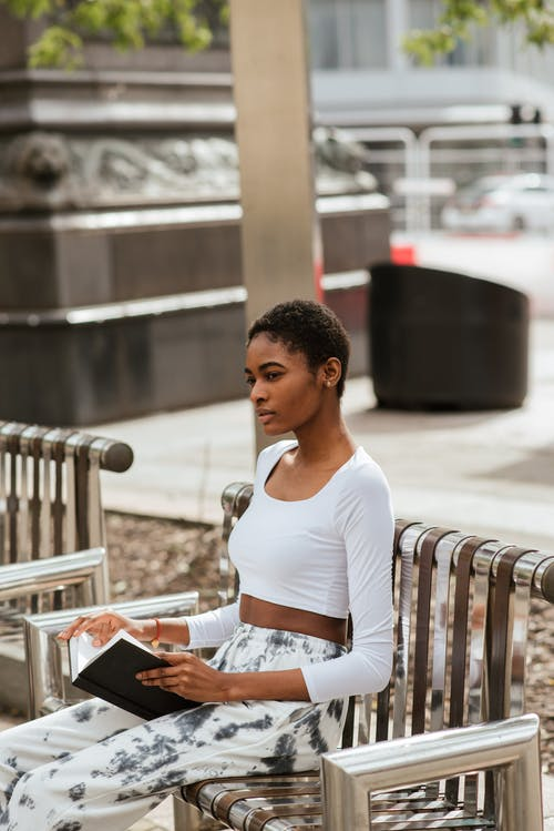 Thoughtful young African American female in white casual clothes with short dark hair sitting on bench in park and thinking over open book