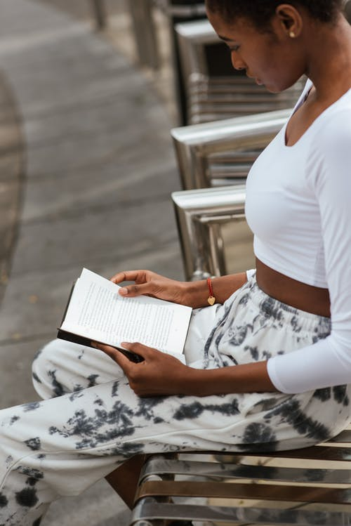 Crop attentive black woman reading book on street bench