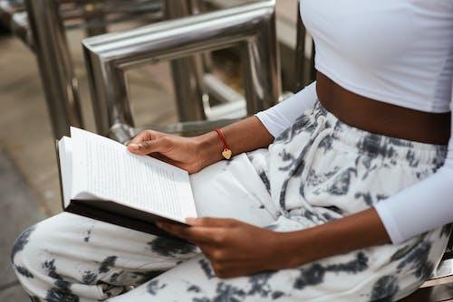 Crop black woman reading book on street bench