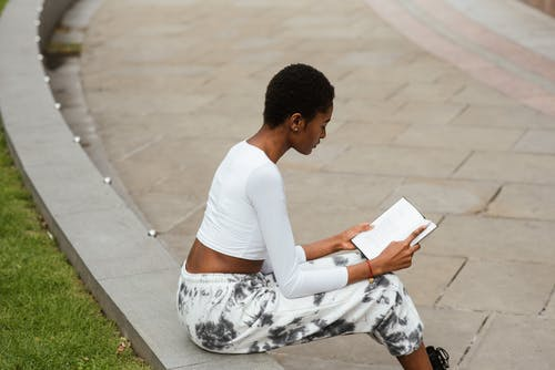 Focused African American woman reading textbook on street