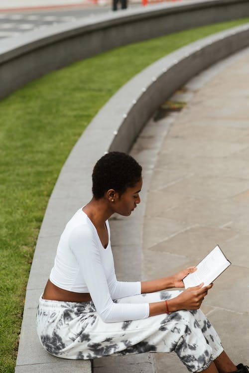 High angle side view of young black female in casual wear reading textbook on urban pavement near lawn