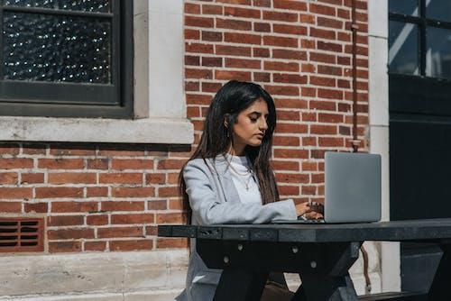 町のラップトップで入力する気配りのある民族の女性起業家
