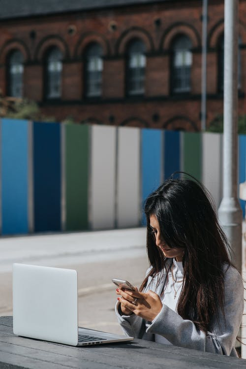 Ethnic female entrepreneur chatting on smartphone at table with laptop