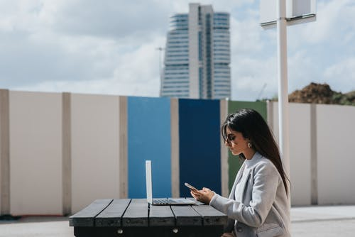 Ethnic female executive watching smartphone at table with laptop outdoors