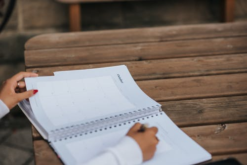 Crop anonymous female student writing in planner while sitting at wooden table in park
