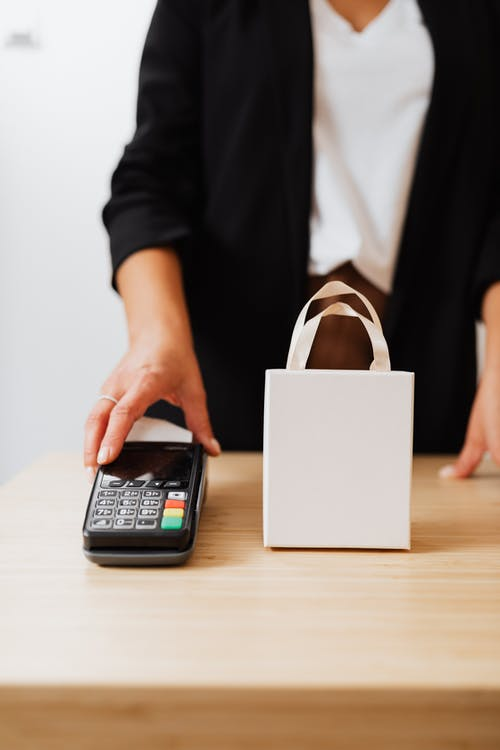 A Person Holding Payment Terminal on Brown Wooden Counter