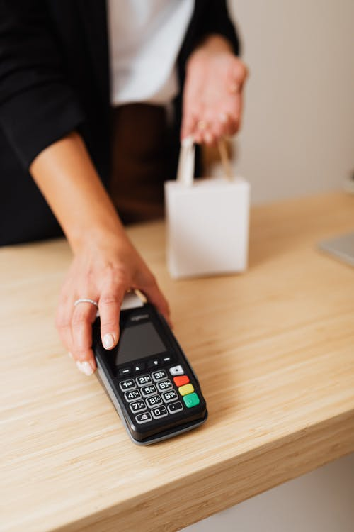 Person Holding Black Payment Terminal and White Paper Bag on Wooden Table