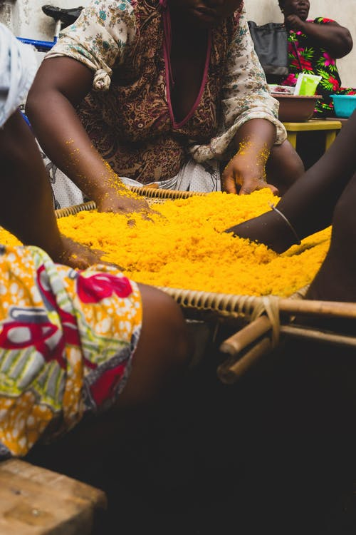 Crop African vendors mixing vibrant yellow colored spice in box while selling grocery in local crowdy bazaar