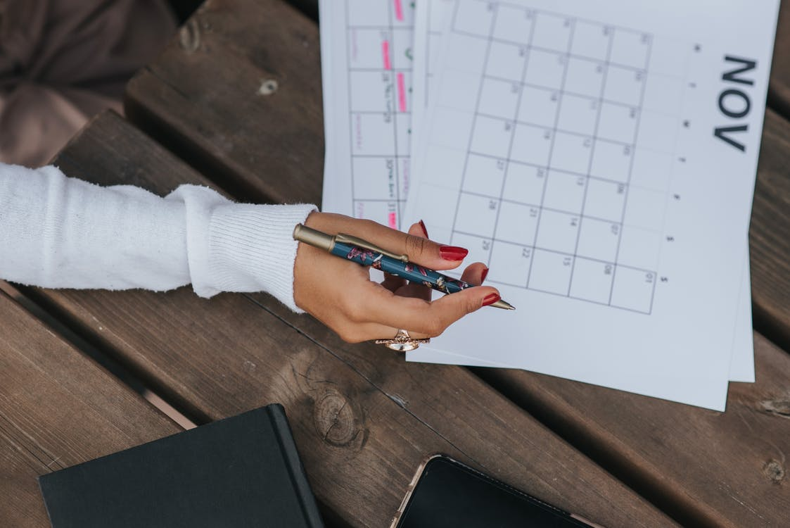 From above of crop anonymous female in white blouse sitting at wooden table with pen and calendar while making schedule
