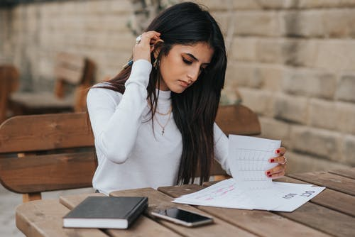Ethnic young woman reading notes