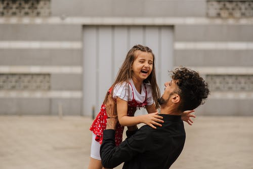 Man carrying smiling little girl in arms and laughing on city street in summer day