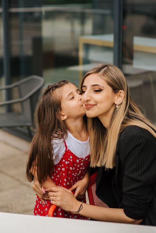 Little girl standing in casual outfit and kissing adult woman on cheek in summer day on city street