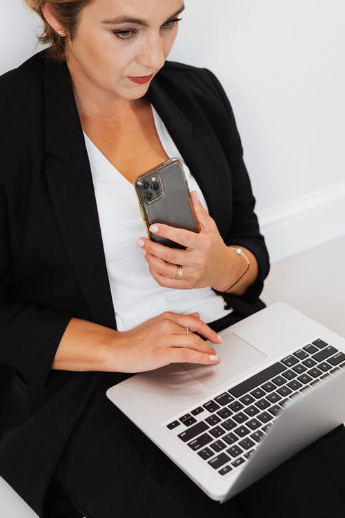 Woman Working on Laptop while Holding Phone