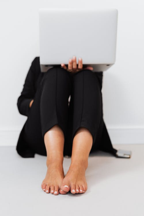 Person in Black Pants Sitting on the Floor