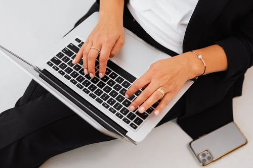 Hands of Person Typing on Laptop
