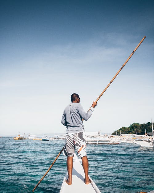 Man in White Shirt and White Shorts Fishing on Sea