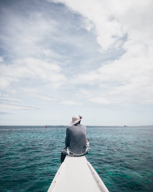 Man in Grey Shirt and White Shorts Sitting on White Boat