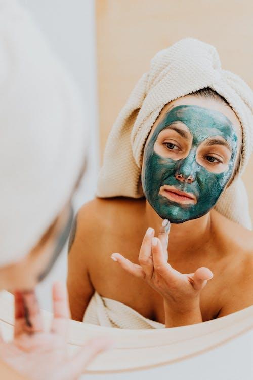 Woman Applying a Green Facial Mask