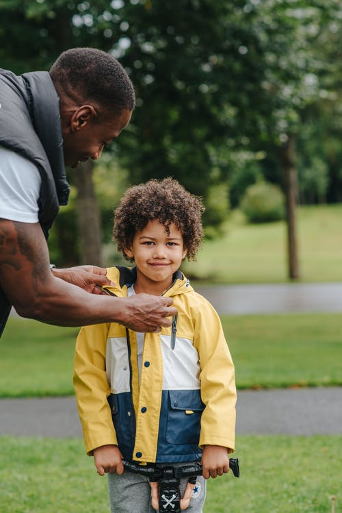 Black father putting on jacket on son