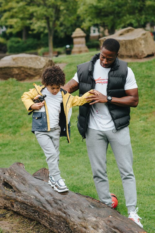 Black son walking on log near father