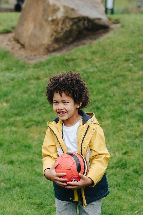 Delighted African America kid with Afro hair looking away while standing on green meadow with football in hands