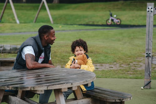 Cheerful black father and son sitting at table in park