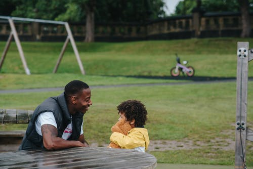Happy black son and father sitting in park