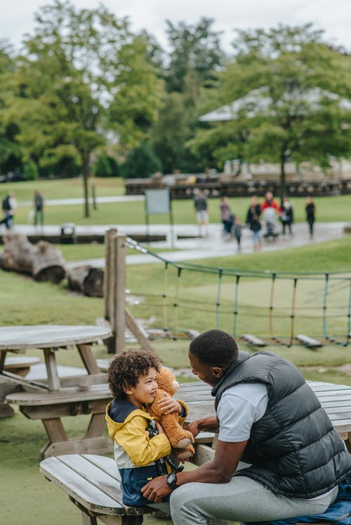 Black father and son looking at each other in park