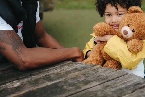 Adorable African American son hugging plush bear at wooden table with unrecognizable black father in park on blurred background