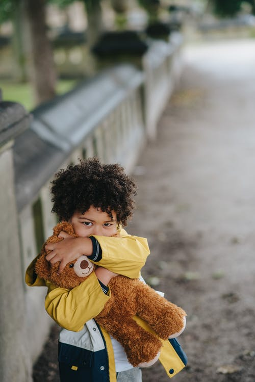 From above of African American little boy looking at camera and hugging teddy bear while standing on street near fence on blurred background