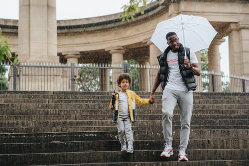 Full body of African American kid and man with umbrella walking on steps while holding hands near ancient structure with column in rainy weather