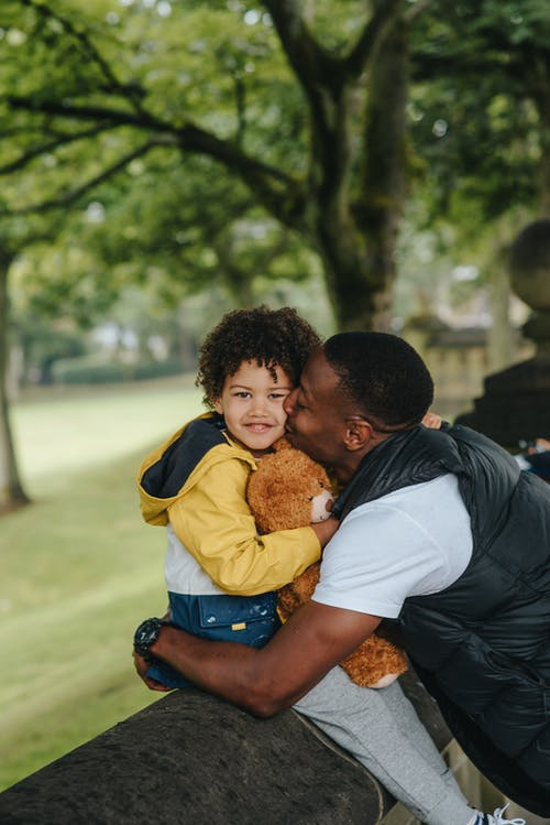 Side view of African American father hugging and kissing toddler boy carrying cute toy bear while sitting on concrete fence and smiling at camera