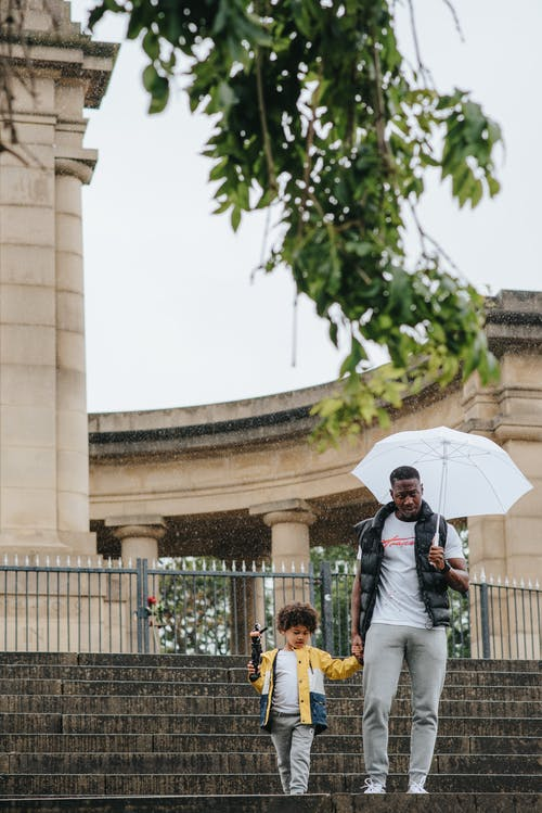 Young black man with umbrella walking downstairs with son