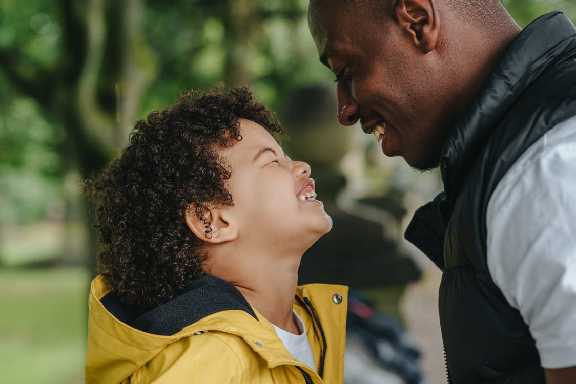 Side view of African American young father smiling while looking on joyful little son with closed eyes on blurred background