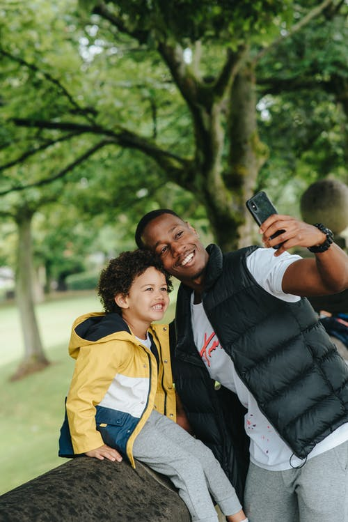 Happy black father with son taking selfie on smartphone outdoors