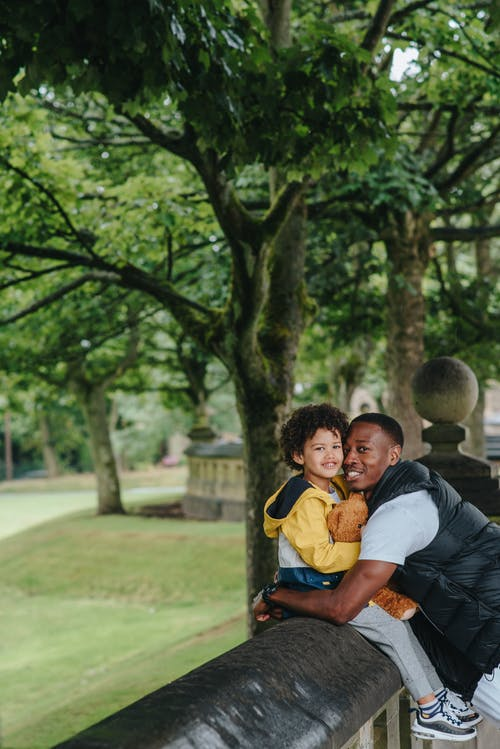 Side view of content African American man embracing son in casual wear while looking at camera in town