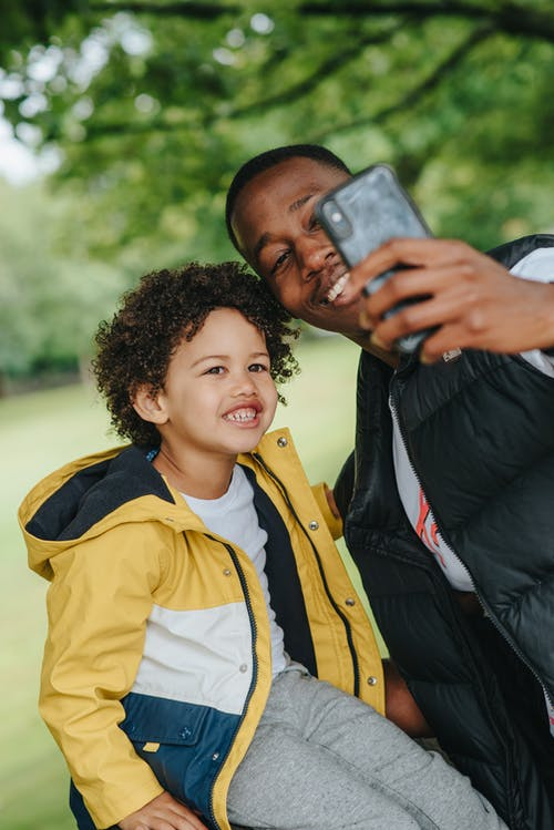 Young cheerful African American father with friendly kid taking selfie on cellphone in city park