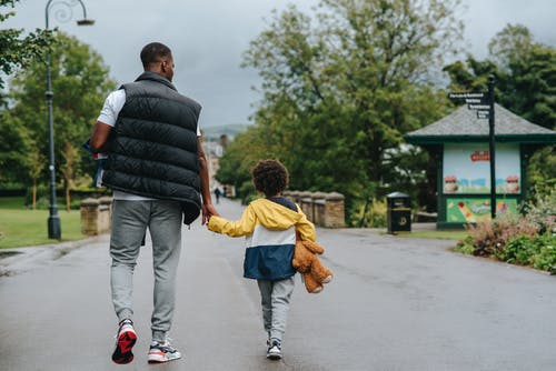 Back view of anonymous African American man holding child by hand while walking on urban roadway in daylight