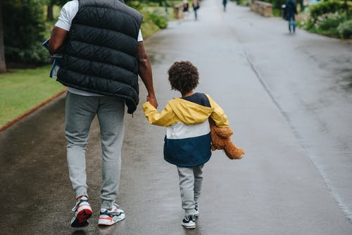 Crop black man with son holding hands strolling on roadway