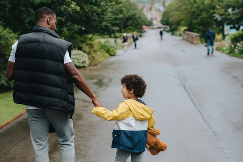 Back view of anonymous African American man holding cheerful son by hand while looking at each other on urban road