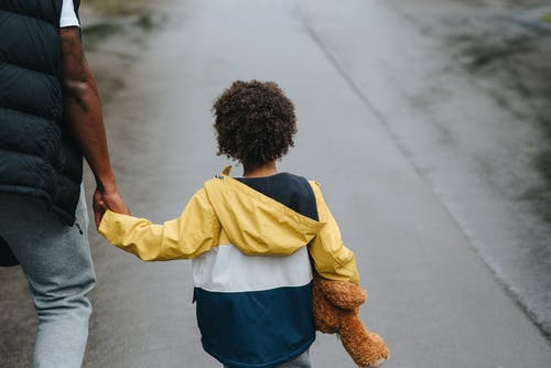Crop black man with son holding hands on road