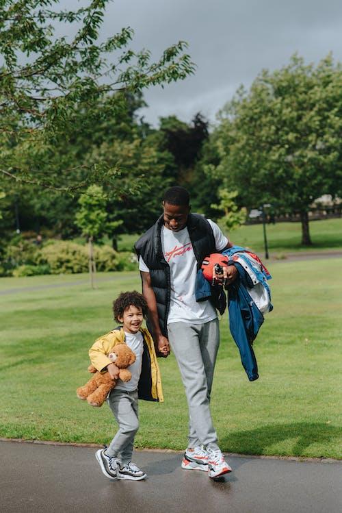 Zwarte Man Met Gelukkige Jongen Lopen Op Weg In De Buurt Van Park